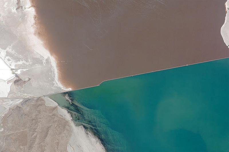 Вид из космоса на Большое соленое озеро, разделенное насыпью с железной дорогой. Северная половина озера розовая от населяющих ее микроорганизмов, соленость в ней примерно в два раза выше, чем в южной. Фото: Axelspace Corporation / CC BY-SA 4.0