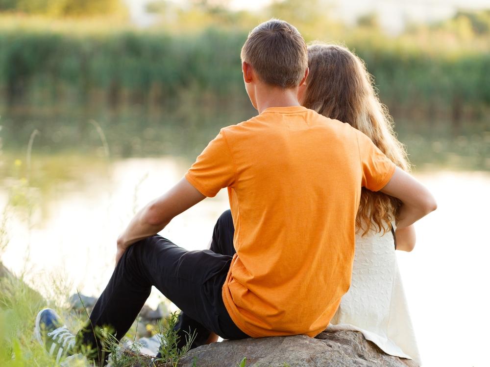 пара сидит обнявшись на берегу