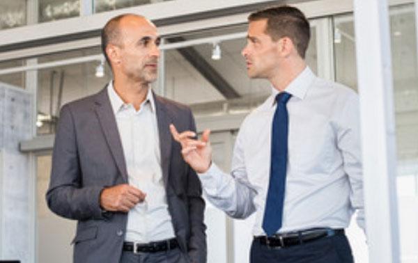 Два мужчины общаются. Один жестикулирует рукой